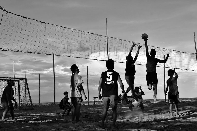 Men playing volleyball against sky