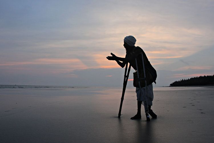 Full length of silhouette man with crutches standing at beach against sky during sunset