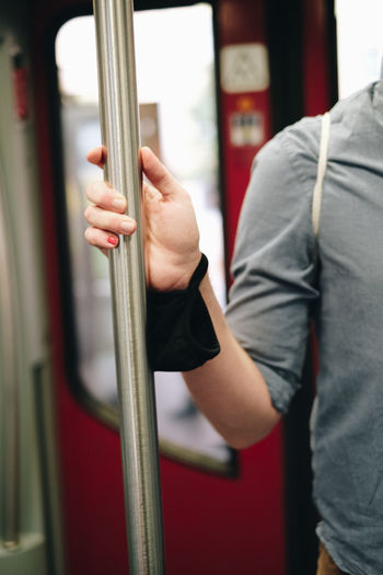 Midsection of man holding metallic pole in train