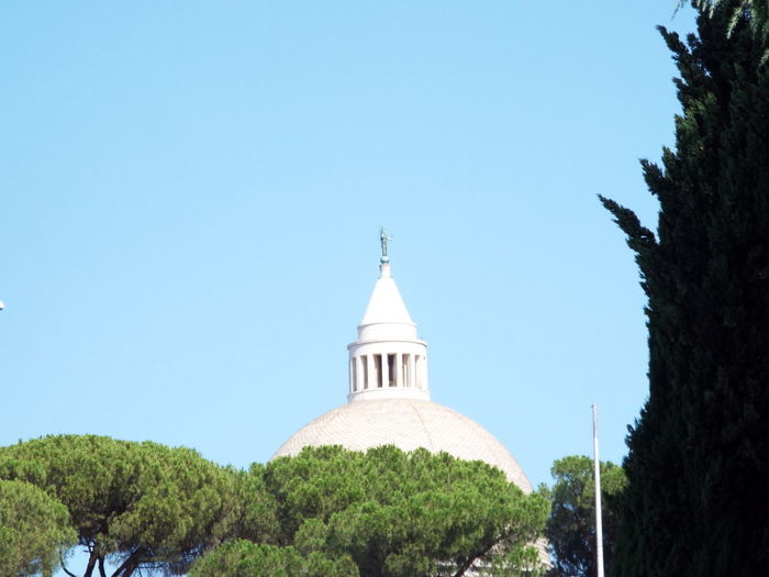 Panoramic view of trees and building against clear blue sky