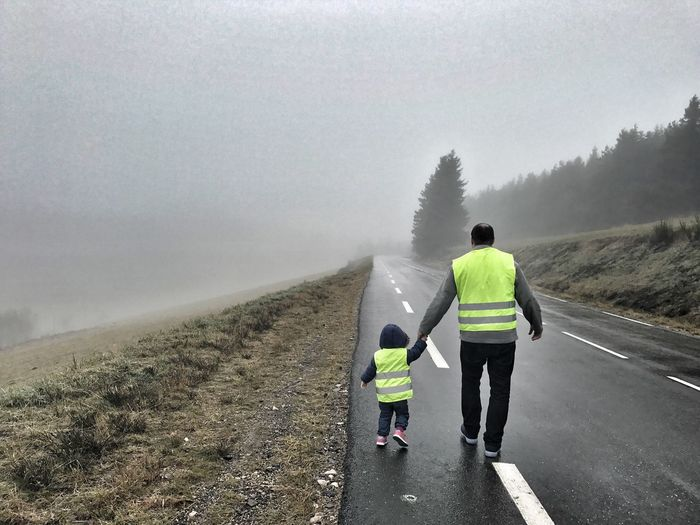 Rear view of man and child on road against sky