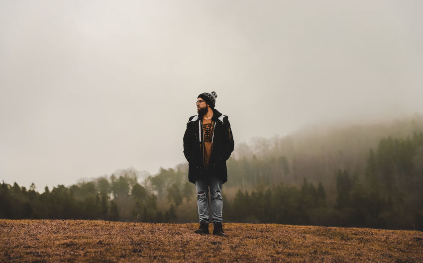 Man standing on field against foggy sky