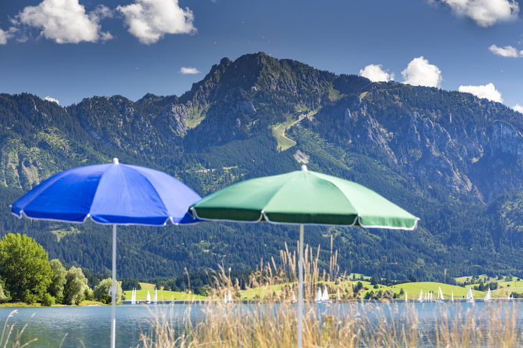 Parasols by forggensee lake against tegelberg mountain