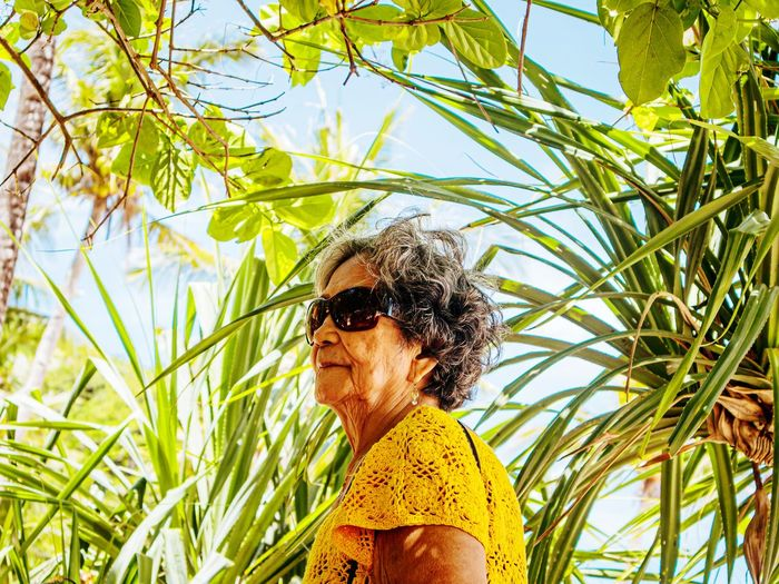 Portrait of woman wearing sunglasses standing against plants