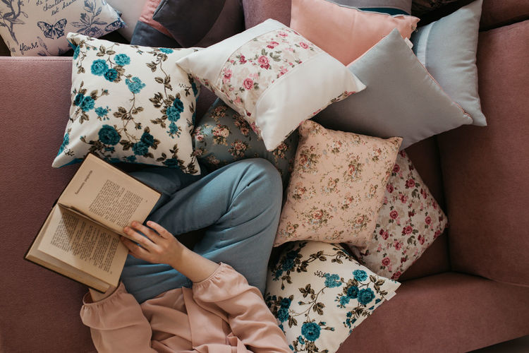 Directly above shot of woman reading book sitting on sofa at home