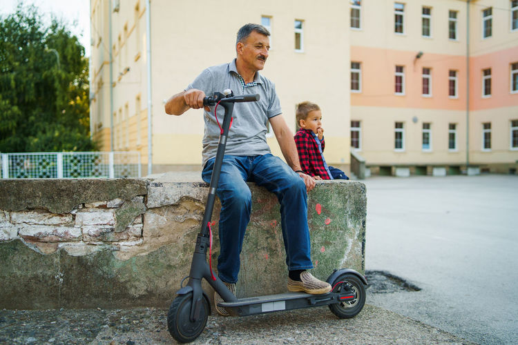 Father and son with push scooter sitting on retaining wall