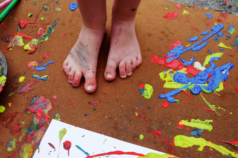 Low section of child standing on surface with messy paint
