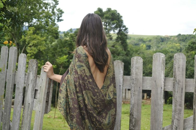 Rear view of woman with scarf standing by fence at park