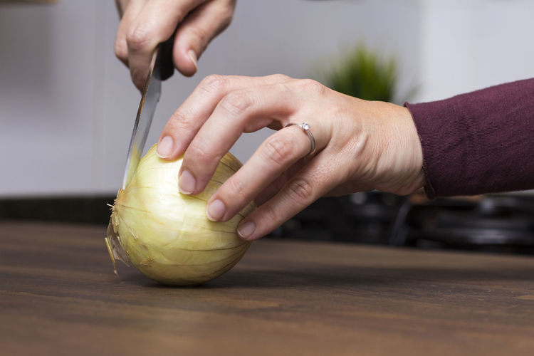 Cropped hands of woman cutting onion on wooden table