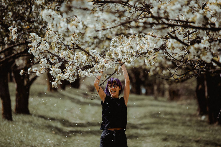 Full length of woman standing by cherry blossom tree