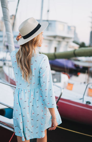Beautiful blonde young woman in blue dress and straw hat on boat at pier in the sunset time