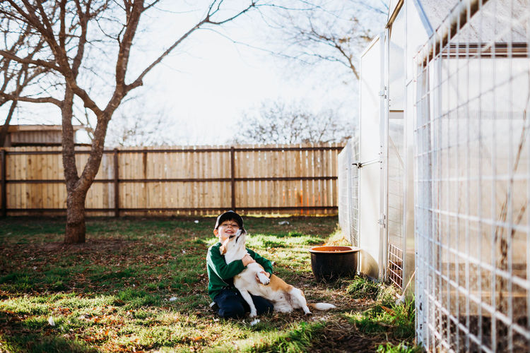 Young woman with dog standing by fence against trees