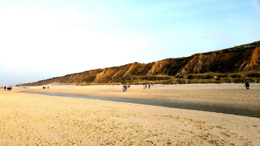 Tourists walking on beach in sylt island