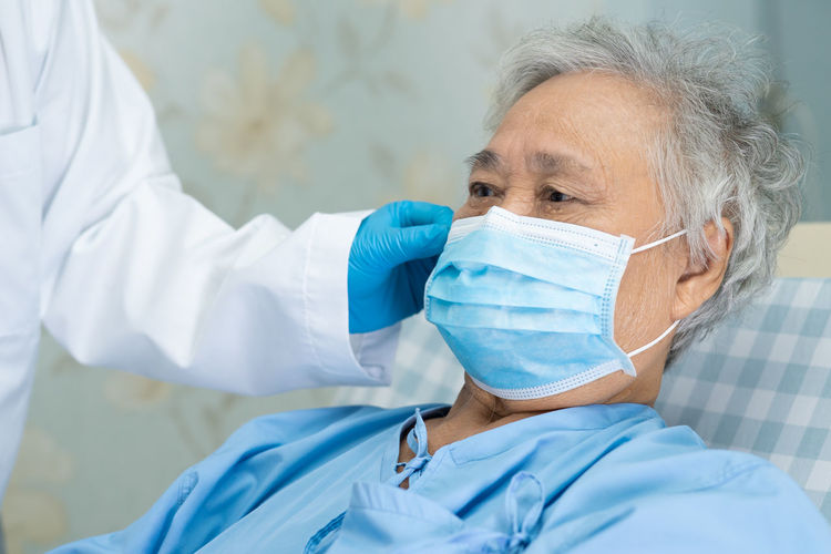 Midsection of doctor wearing mask to senior woman in hospital