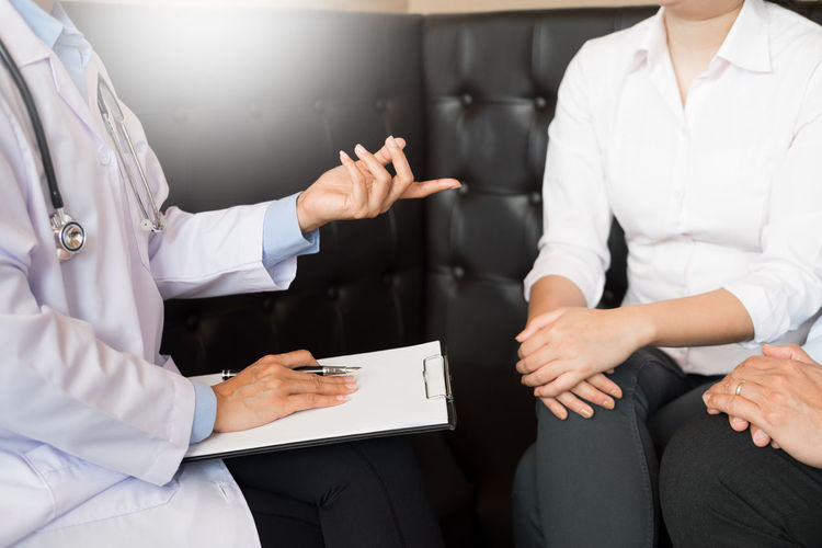 Midsection of female doctor talking with patient