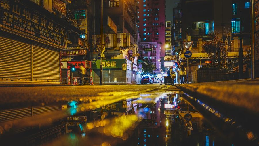 Reflection Of Illuminated Buildings On Puddle At Night