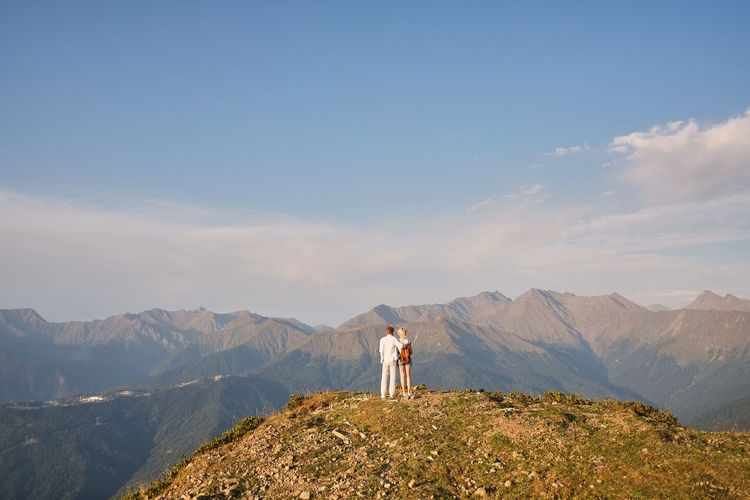 Rear view of couple standing on mountain peak against sky