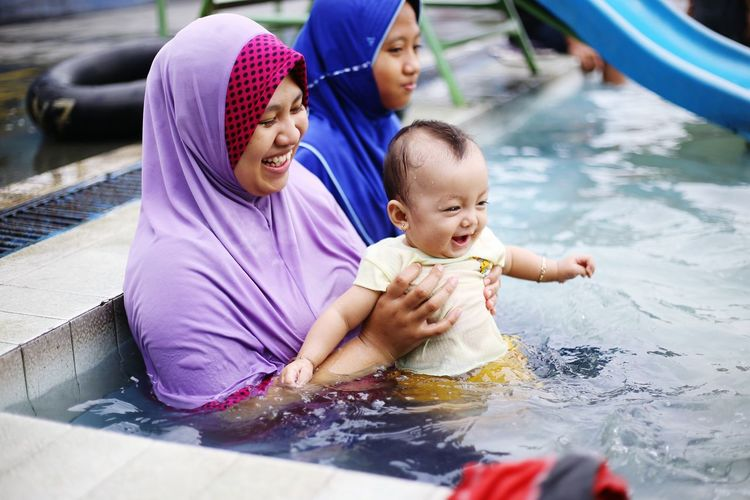 Smiling woman with daughter and sister sitting in pool
