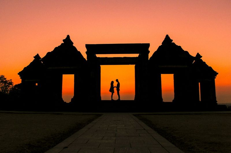 Silhouette man and woman standing at ratu boko against clear sky during sunset