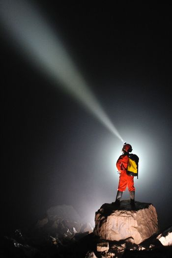 Rear view of person standing on rock against sky at night