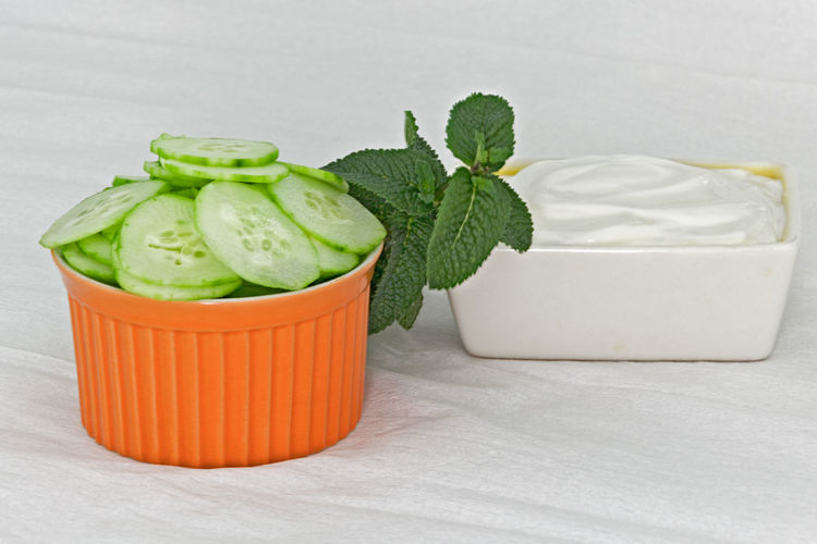 Close-Up Of Sliced Cucumber With Cheese Spread On Table