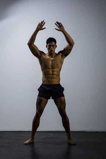 Shirtless Muscular Man Exercising Against Wall