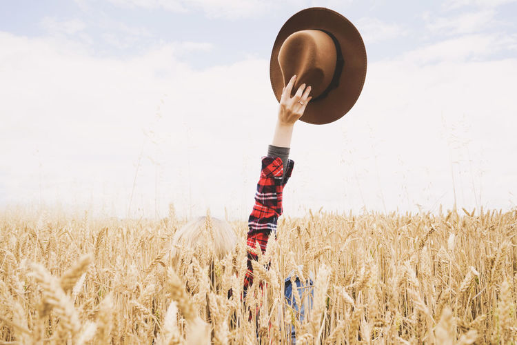 Land Field One Person Landscape Sky Plant Real People Crop  Agriculture Nature Cloud - Sky Cereal Plant Human Body Part Rural Scene Leisure Activity Scenics - Nature Lifestyles Standing Growth Outdoors Arms Raised Human Limb Happiness Hat Countryside