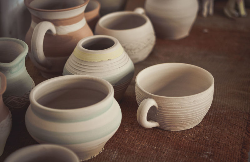 Many clay pot is on the table in pottery. bright pottery. many white, not painted clay pottery