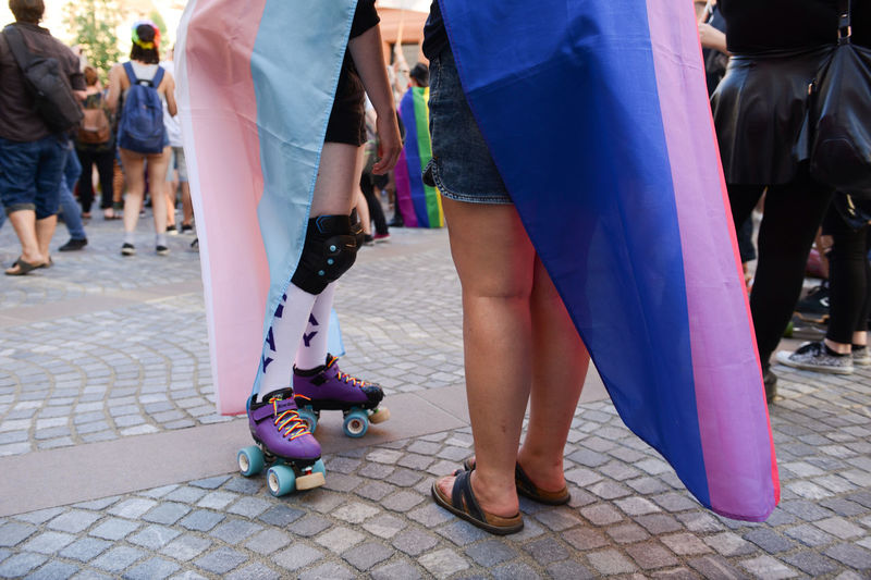People wearing rainbow flag during parade in city
