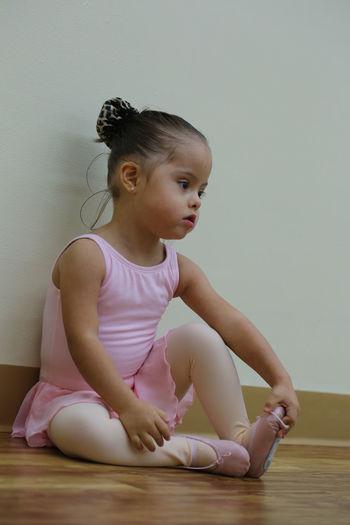 Ballet dancer girl sitting on floorboard against wall