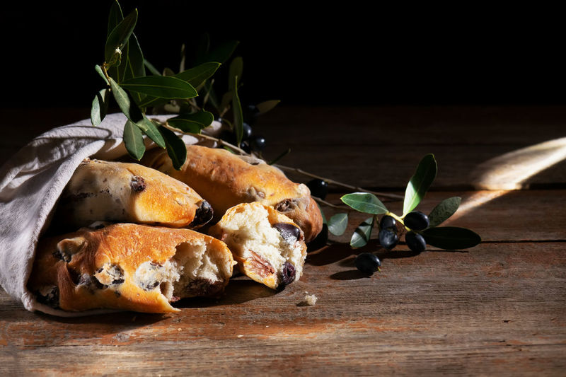 Traditional italian puccia bread with black olives in a cotton bag on a wooden background