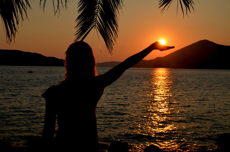 Silhouette Hand Holding Sun Against Sky During Sunset Sunset Silhouettes Arms Raised Beach Beauty In Nature Hand Horizon Over Water Human Arm Idyllic Leisure Activity Lifestyles Nature One Person Orange Color Outdoors Real People Scenics - Nature Sea Sihouette  Sky Sun Sunlight Sunset Tranquil Scene Tranquility Water