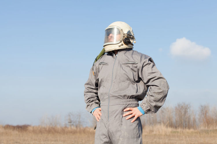 Mid adult man wearing protective workwear standing on field against sky