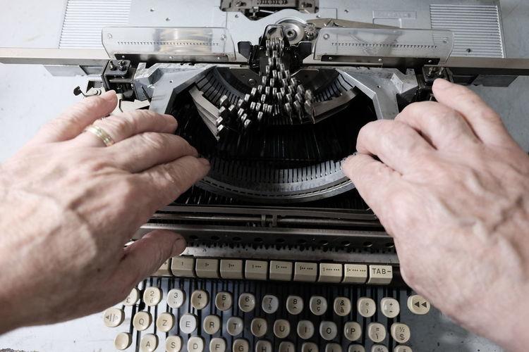 Cropped Hands Repairing Typewriter