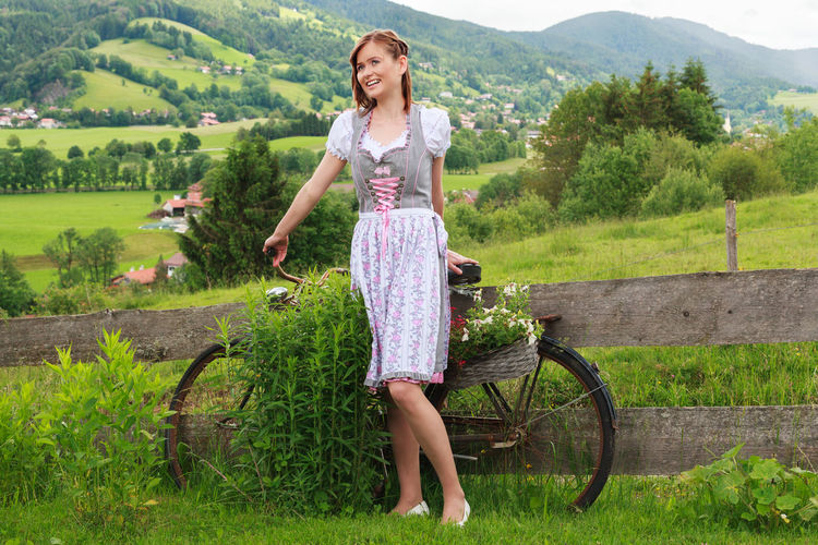 Young woman with bicycle standing on grassy field