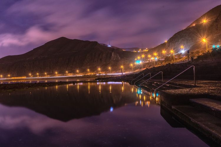 Reflection of illuminated mountain in natural swimming pool at the sea with sky at night