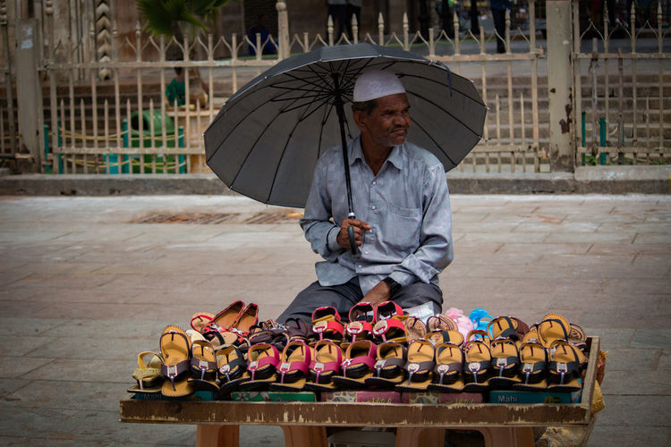 Vendor Holding Umbrella While Selling Sandals At Market