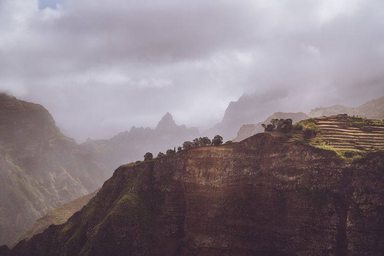 Scenery with shape of huge rocks and motion clouds mist on sky. Surreal moment before a thunderstorm in the mountains on Santo Antao Cape Verde. Beauty In Nature Climate Cloud - Sky Day Environment Fog Formation Haze Landscape Moody Mountain Mountain Peak Mountain Range Nature No People Non-urban Scene Outdoors Rock Rock Formation Scenics - Nature Sky Tranquil Scene Tranquility Travel Travel Destinations