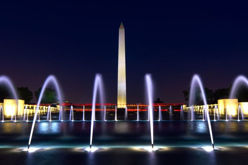 Blurred motion of illuminated fountain against monument at night