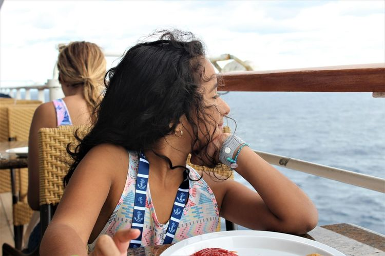 Girl Looking Away While Sitting At Table In Ship
