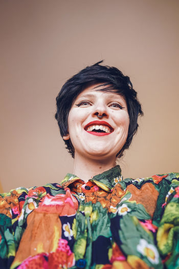 Smiling woman with make-up against colored background