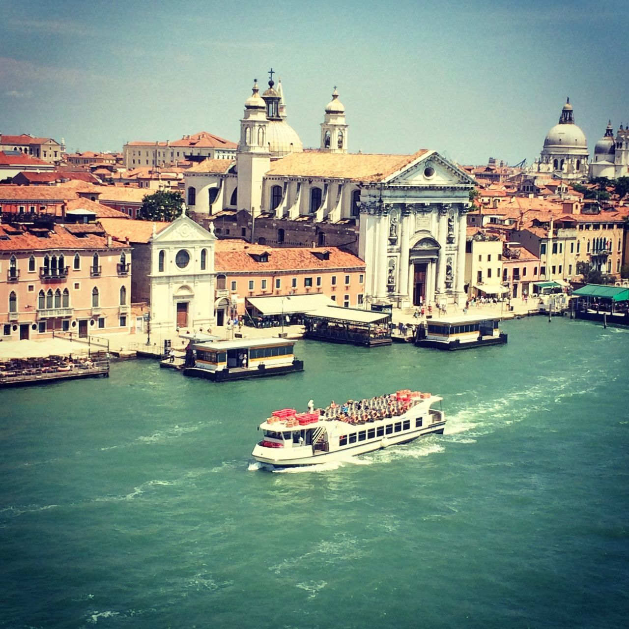 architecture, religion, place of worship, building exterior, nautical vessel, dome, built structure, spirituality, transportation, water, travel destinations, mode of transport, travel, waterfront, outdoors, day, clear sky, city, no people, gondola - traditional boat, sky