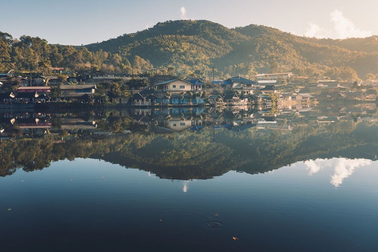 Villages and lakes Baan Rak Thai is little village that surrounds a small lake Building Exterior Water Architecture Built Structure Building Reflection Waterfront Mountain Sky Residential District Nature Lake House City Town Tree No People Plant Beauty In Nature Outdoors TOWNSCAPE