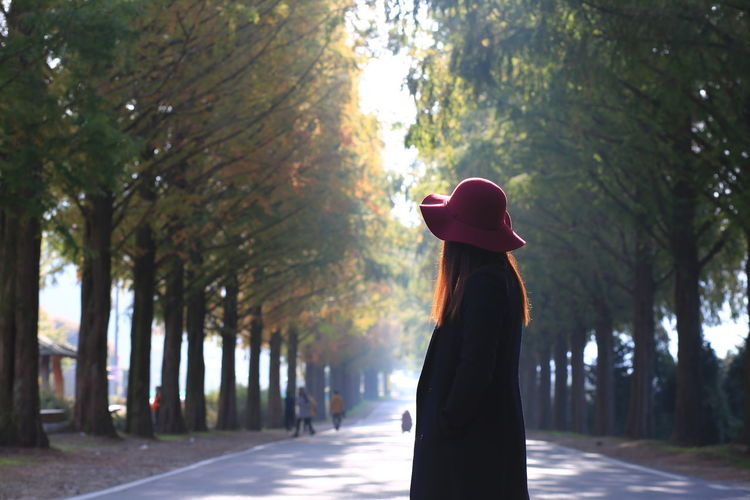 Side view of woman standing by trees