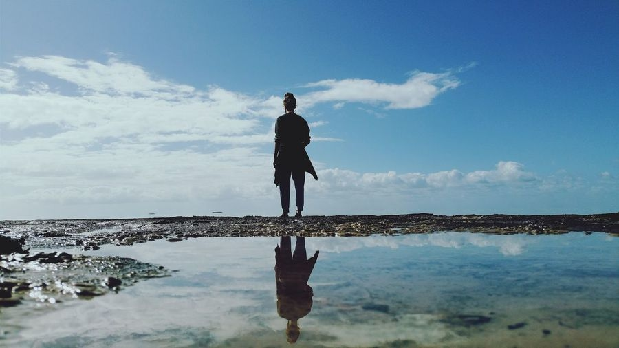Rear view of man standing at sea shore against sky
