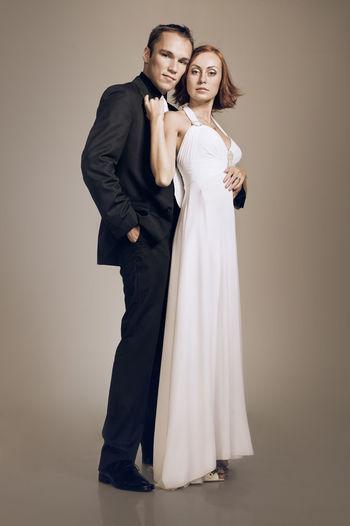 Full Length Portrait Of Couple Standing Against Gray Background