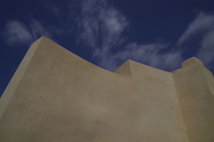 Low angle view of building against cloudy sky