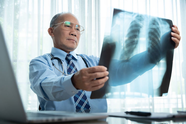 Asian Senior Male doctor in blue shirt looking to x-ray film of his patient at a medical room. Adult Asian  Cancer Care Diagnosis Film Hospital Man Check Up Chest Clinic Disease Doctor  Elderly Exam Health Illness Lung Medical Older  Patient Prescription  Senior Stethoscope  X-Ray