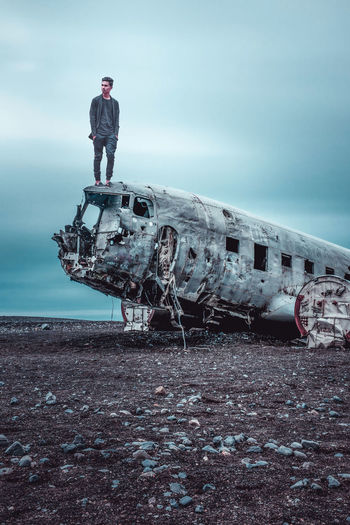 Man standing on old abandoned airplane against cloudy sky
