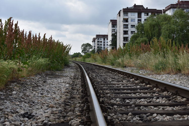 Railroad track amidst buildings against sky
